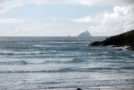 A surfer in St Finian's Bay with Skellig Michael in the background, County Kerry.